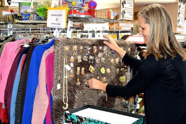 Blonde woman buying donated clothes from a thrift store